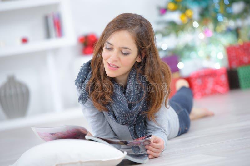 Fille songeuse attirante reposant et lisant le magazine images libres de droits