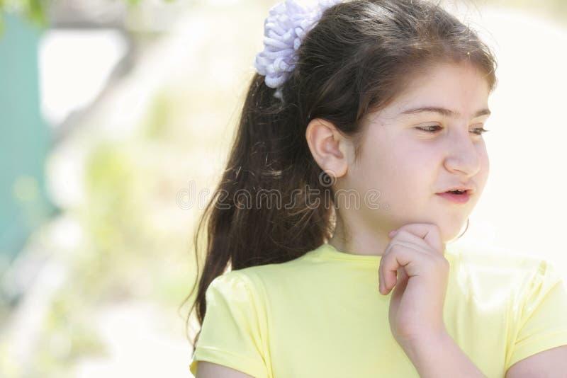 Fille songeuse de brunette dans la chemise jaune images stock