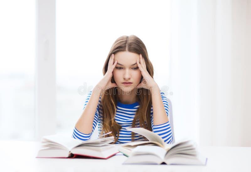 Fille soumise à une contrainte d'étudiant avec des livres image stock