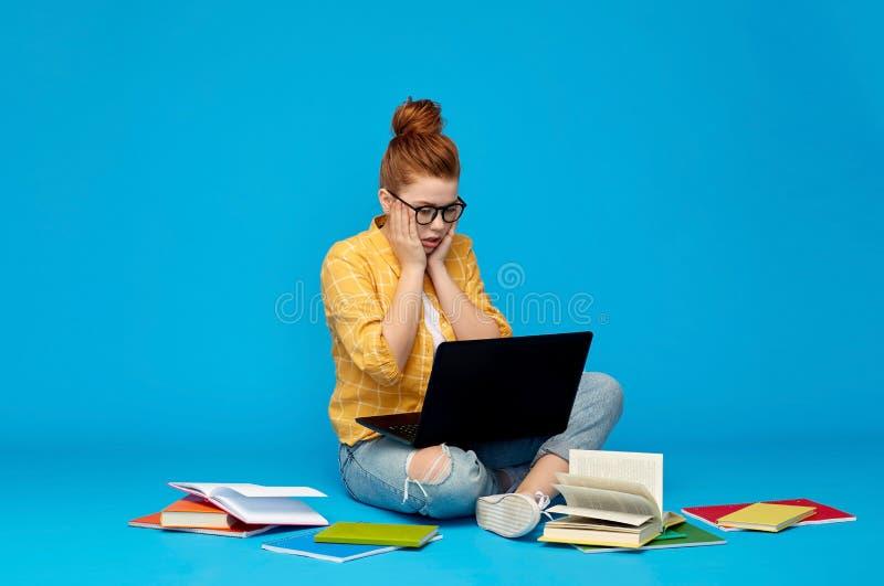 Fille soumise à une contrainte d'étudiant avec l'ordinateur portable et les livres images stock