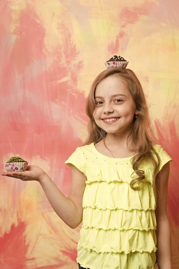 Fille souriant avec des petits gâteaux à disposition et sur la tête photographie stock