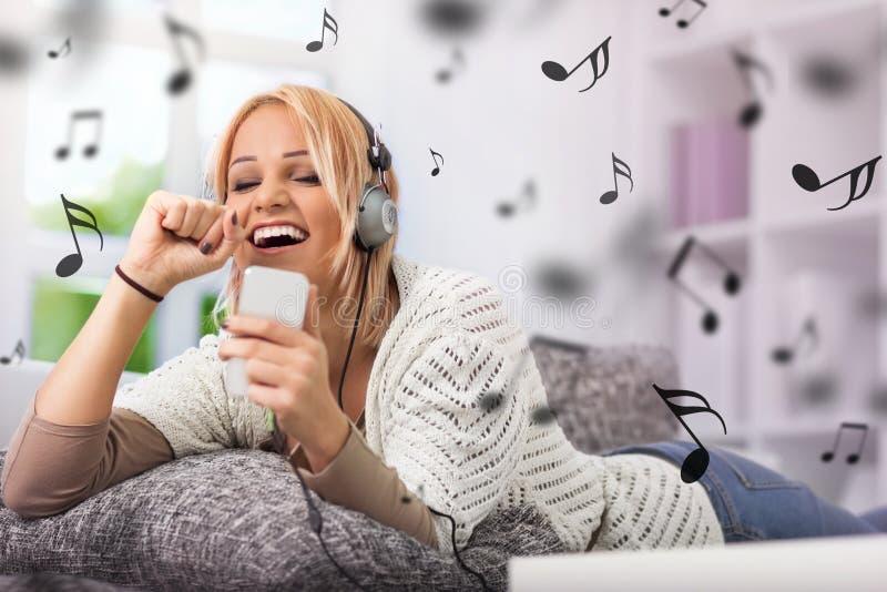Fille souriant et chantant avec son téléphone et écouteurs image stock