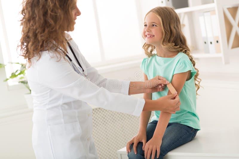 Fille souriant tandis que pédiatre collant le plâtre de cour images libres de droits