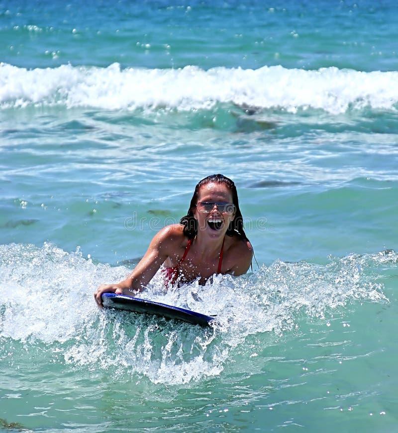 Fille souriant tout en conduisant une grande onde bleue sur un panneau de fuselage sur la mer bleue un jour ensoleillé. photographie stock libre de droits