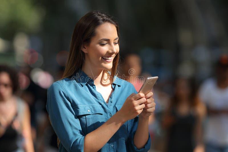 Fille souriante à l'aide d'un téléphone intelligent marchant dans la rue photo libre de droits
