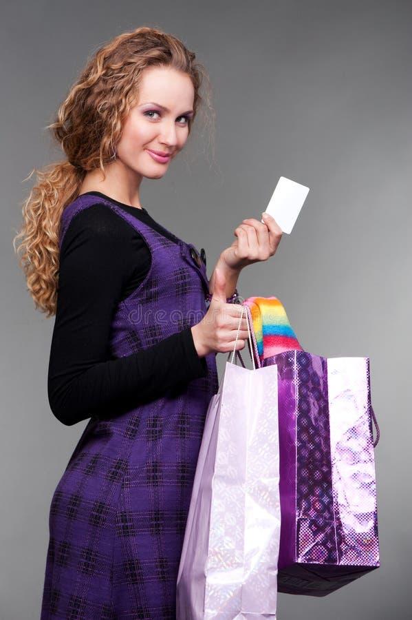 Fille souriante avec par la carte de crédit et des sacs en papier images libres de droits