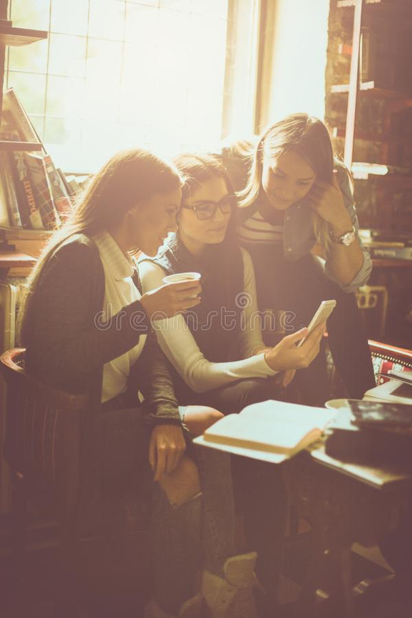 Fille souriante de trois étudiants en café utilisant le téléphone intelligent image libre de droits