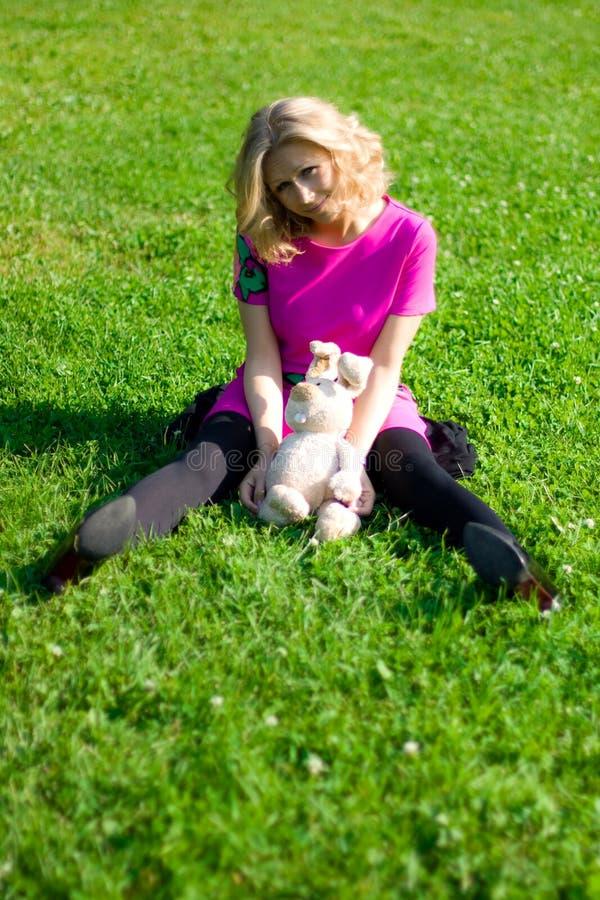 Fille souriante sur l'herbe avec le jouet-lapin photos libres de droits