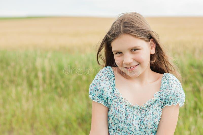 Fille sourie peu sur le fond de champ de blé photographie stock