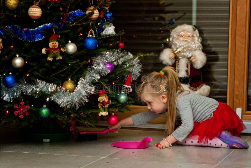 Fille sous des aiguilles de nettoyage d'arbre de Noël photos libres de droits