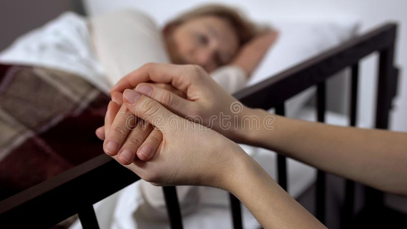 Fille soutenant sa terminalement m?re de d?fectuosit? se trouvant sur le lit d'h?pital, hospice images stock