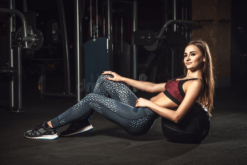 Fille sportive de belle forme physique la jeune se trouve sur la boule fléchissant des muscles abdominaux image libre de droits