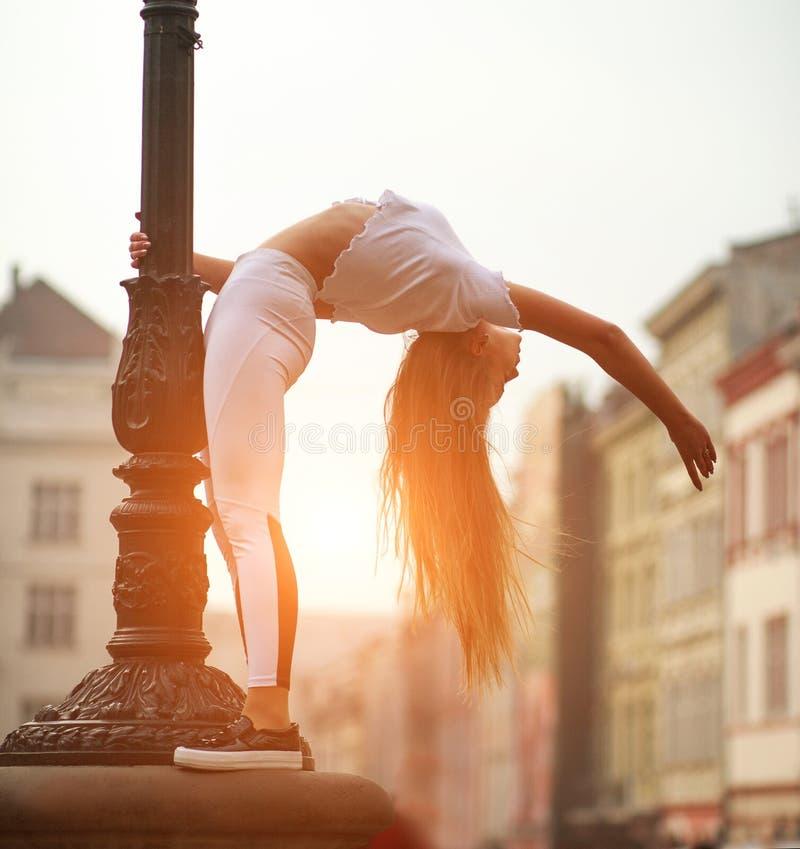 Fille sportive de gymnaste de sport faisant la séance d'entraînement s'étendant sur la rue de la vieille ville en été images stock