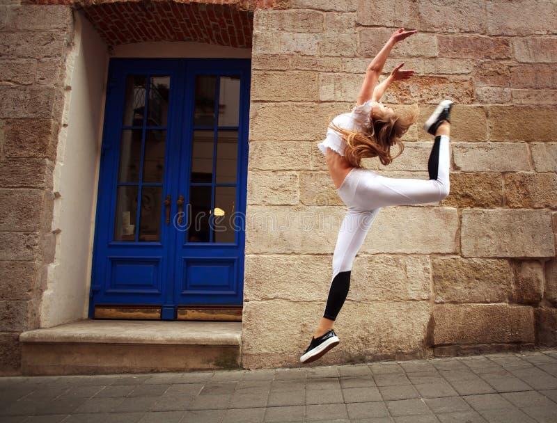 Fille sportive de sport faisant des exercices sautants sur la rue de ville sur le fond du mur en pierre de cru images libres de droits