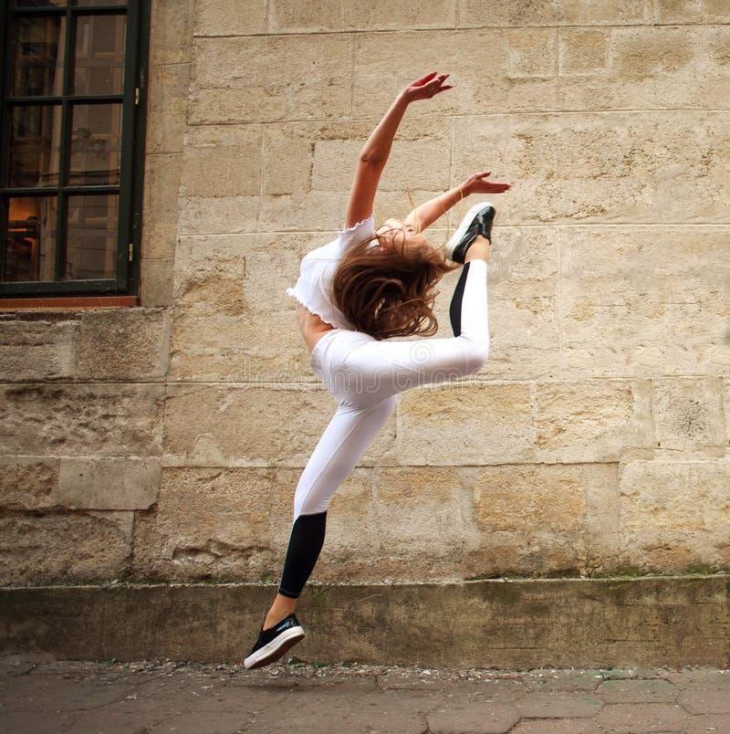 Fille sportive de sport faisant des exercices sautants sur la rue de ville sur le fond du mur en pierre de cru image libre de droits