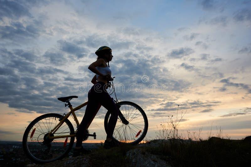 Fille sportive de vue de côté dans le casque avec la bicyclette sur la roche sous le beau ciel de soirée avec des nuages images stock