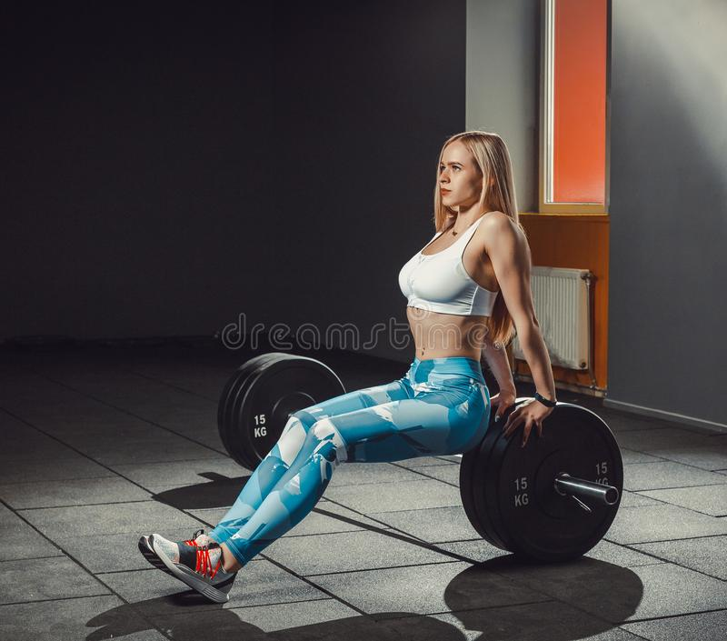 Fille sportive européenne sexy de forme physique établissant dans le gymnase La femme de forme physique s'assied sur le barbell o photos stock