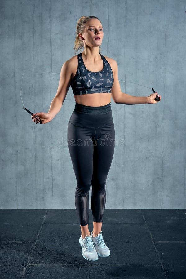 Fille sportive gaie dans la formation de femme de vêtements de sport avec une corde à sauter dans un gymnase sur un mur gris photo stock