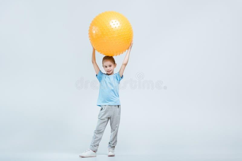 Fille sportive tenant la boule de forme physique sur le blanc image stock