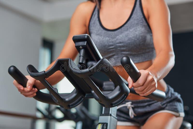 Fille stationnaire de forme physique de bicyclettes dans un club de sport de gymnase image stock