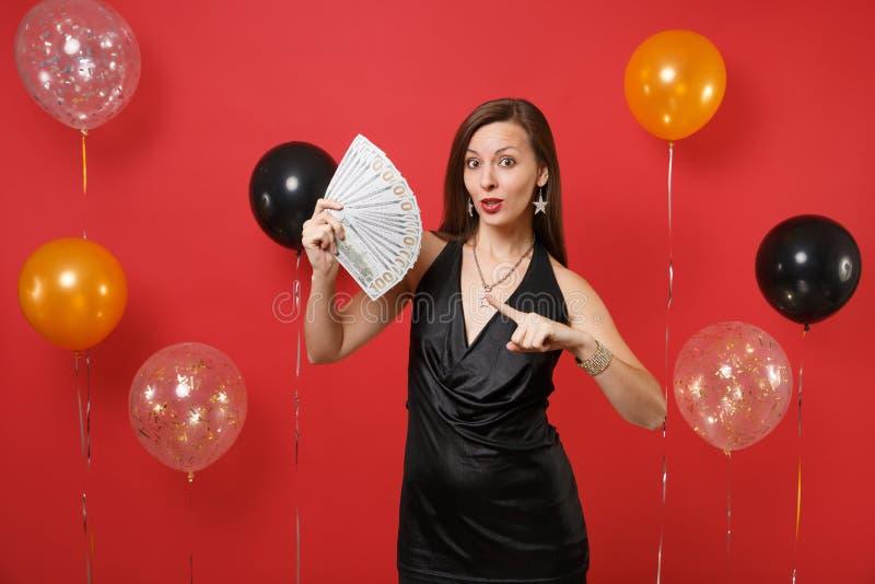 Fille stupéfaite dans la robe noire célébrant dirigeant l'index sur un bon nombre de paquet de dollars, argent d'argent liquide à image stock