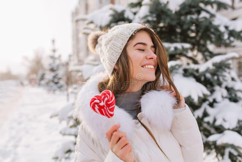 Fille stupéfiante drôle de portrait appréciant l'horaire d'hiver, tenant le lollypop sur la rue Émotions heureuses de Brightful d photos libres de droits