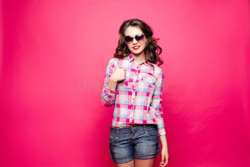 Fille stupéfiante en bref et les lunettes de soleil de port de chemise montrant le signe de paix image stock