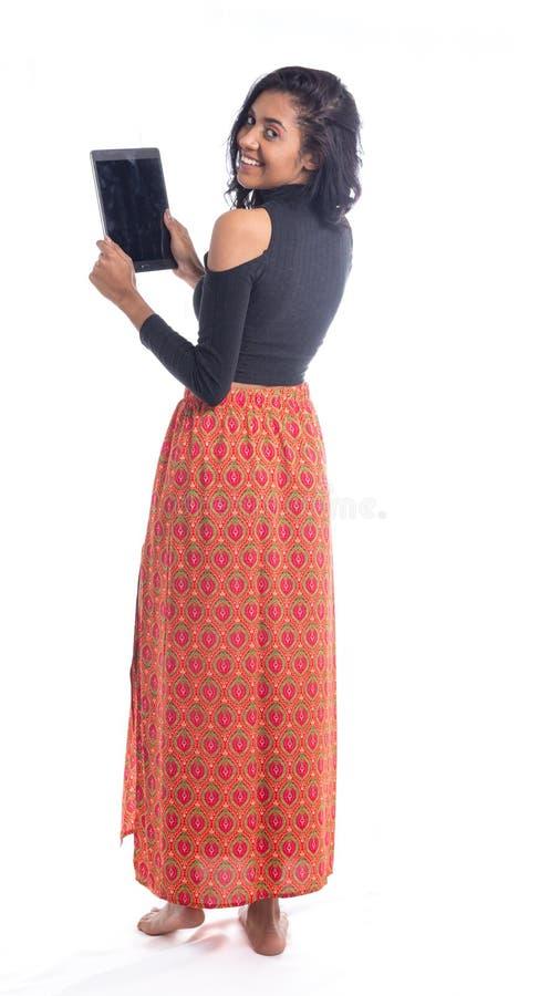 Fille sur elle de retour avec un comprimé dans sa main Femme d'Afrodescendant images stock
