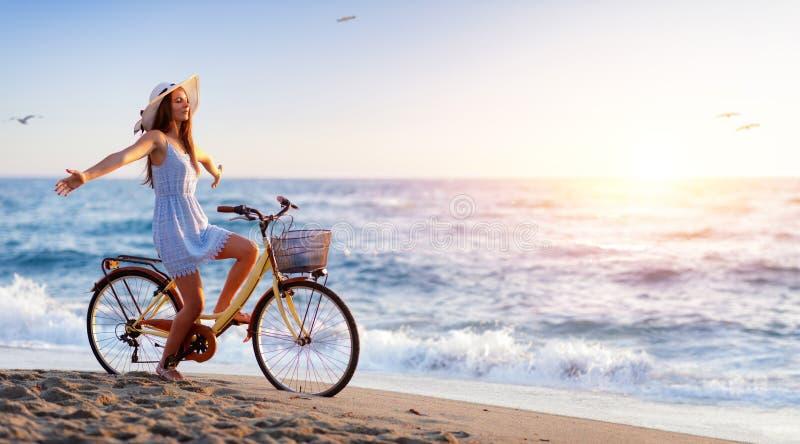 Fille sur la bicyclette sur la plage image libre de droits