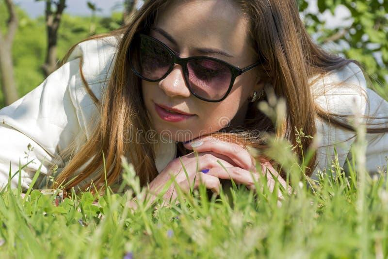 Fille sur la pelouse, le visage du ` s de jeune femme, la fille dans l'herbe photos libres de droits