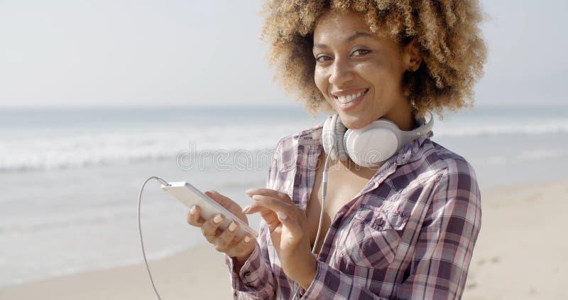 Fille sur la plage écoutant la musique photographie stock