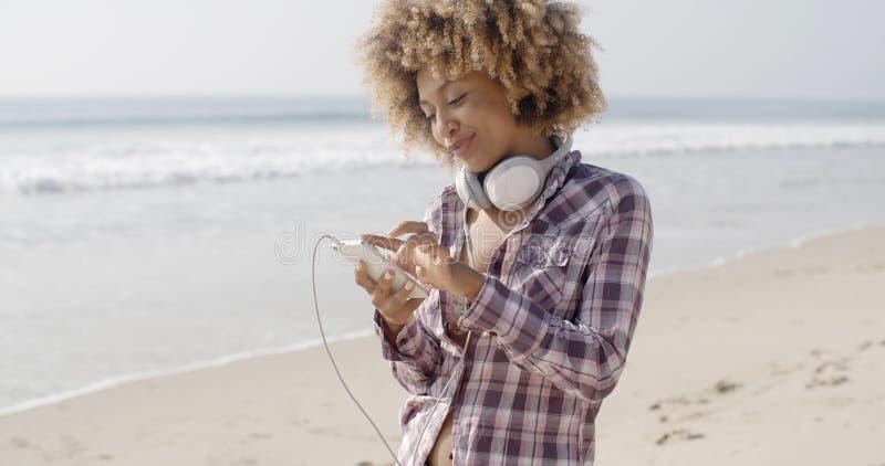 Fille sur la plage écoutant la musique photos stock