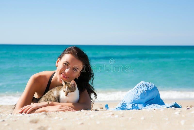 Fille sur la plage avec un chaton image stock