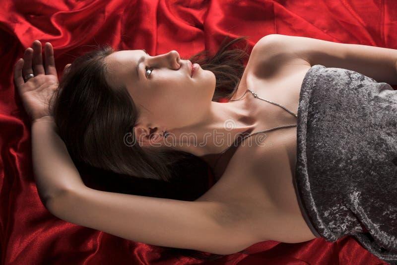 Fille sur la soie rouge photographie stock