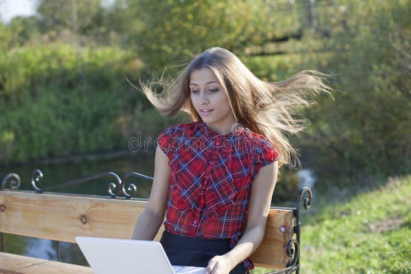 Fille sur le banc avec l'ordinateur portatif photographie stock