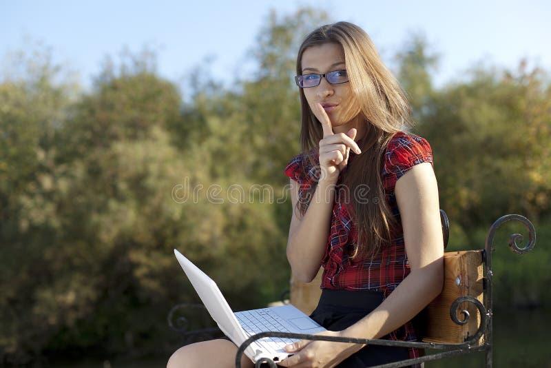 Fille sur le banc avec l'ordinateur portatif - silence photos stock