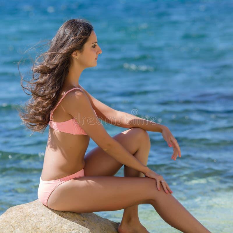 Fille sur le bord de la mer rocheux photographie stock libre de droits