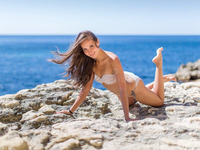 Fille sur le bord de la mer rocheux photographie stock