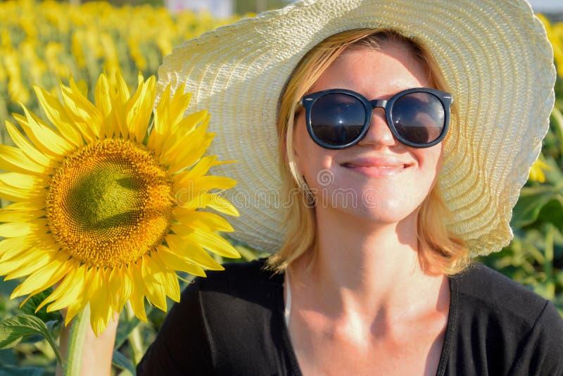 Fille sur le champ des tournesols Fille avec des lunettes de soleil et un chapeau blanc Les fleurs de tournesol image libre de droits