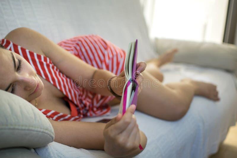 Fille sur le divan lisant un livre photos libres de droits
