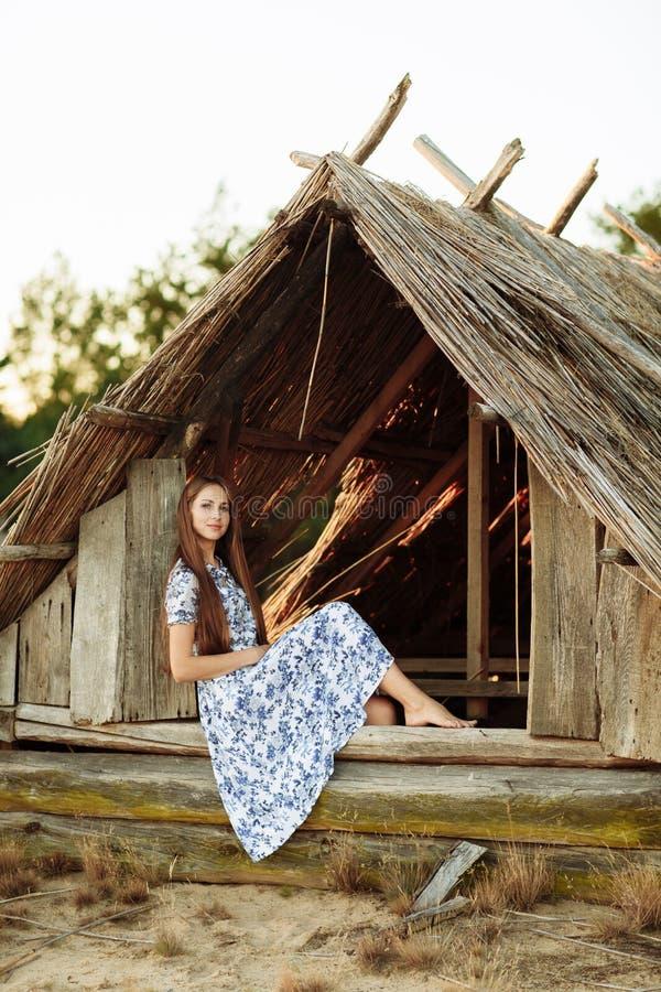 Fille sur le fond d'une vieille maison en bois jetée fille dans la robe blanche avec les fleurs bleues de broderie photo libre de droits