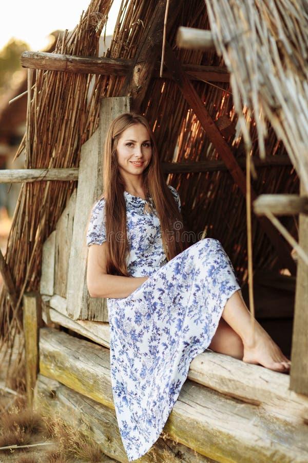 Fille sur le fond d'une vieille maison en bois jet?e fille dans la robe blanche avec les fleurs bleues de broderie image stock