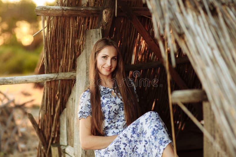 Fille sur le fond d'une vieille maison en bois jet?e fille dans la robe blanche avec les fleurs bleues de broderie images stock