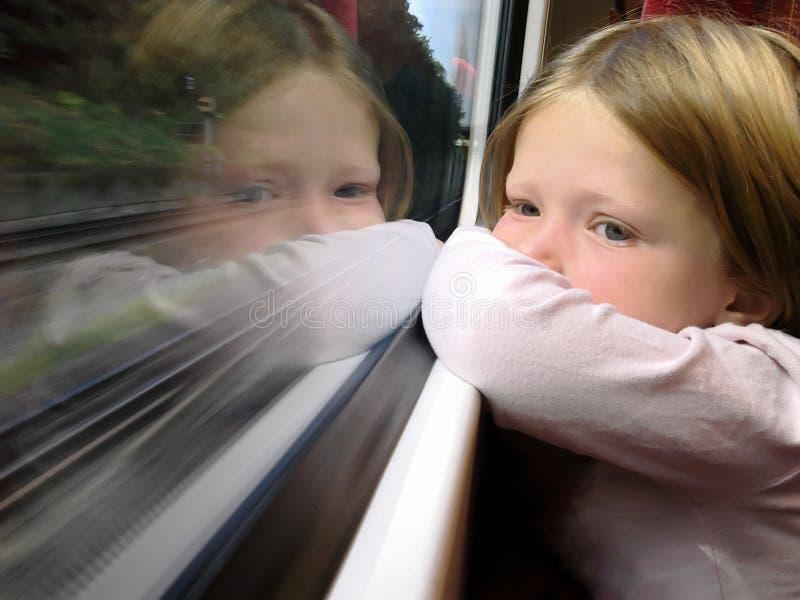Fille sur le train regardant hors de la fenêtre images libres de droits