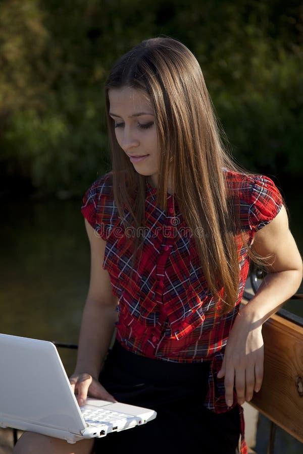 Fille sur le travail de banc avec l'ordinateur portatif image libre de droits