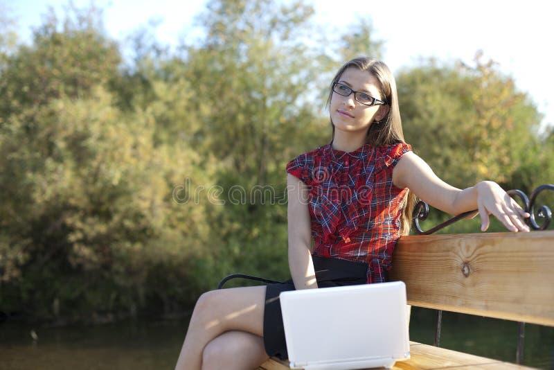 Fille sur le travail de banc avec l'ordinateur portatif photos stock