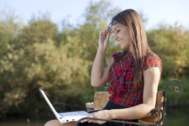 Fille sur le travail de banc avec l'ordinateur portatif photographie stock