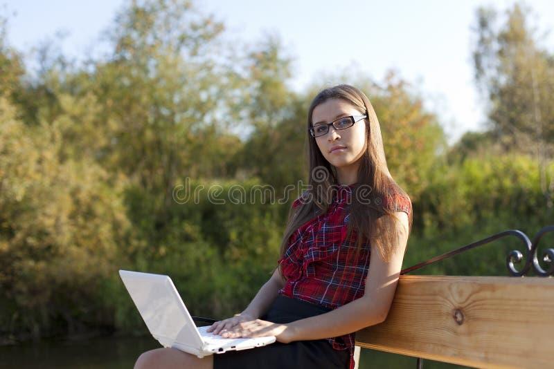 Fille sur le travail de banc avec l'ordinateur portatif images libres de droits