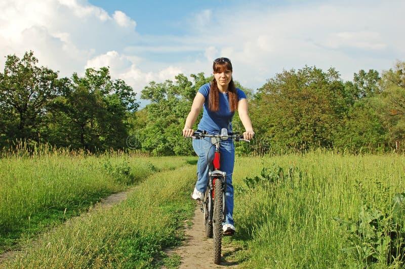 Fille sur le vélo dans le domaine photographie stock