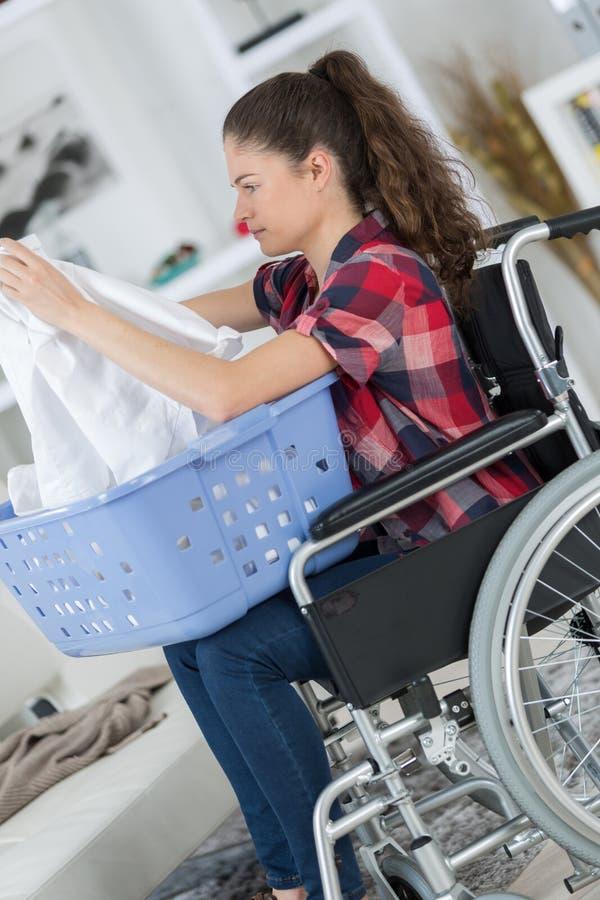 Fille sur les vêtements se pliants de fauteuil roulant image stock